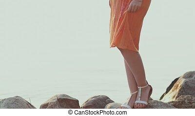 Young girl in orange dress posing at sunset.