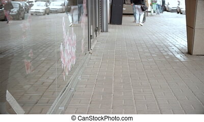 girl in pants runs on the street with packages in hand past shops