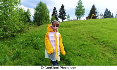 Young girl in raincoat walking and having fun at meadow in...