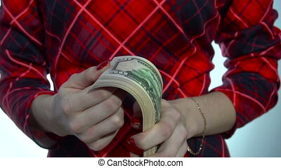 young girl in red dress counts a pack of money in hands in slow motion