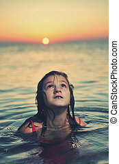 Young girl in red dress standing in sea at sunset