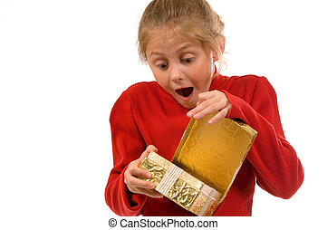 Young girl in red sweater opening Christmas gift wrapped in gold with a look of suprise and excitement