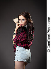 Young sexy girl in red shirt and jeans shorts look at camera
