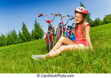 Young girl in red sits on a meadow