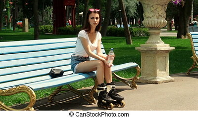 young girl in rollers sitting on a bench in the Park
