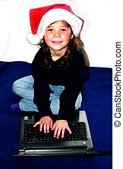 Young girl in santa hat on computer