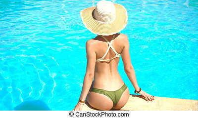 young girl in sexy bathing suit and hat sitting poolside and corrects panties