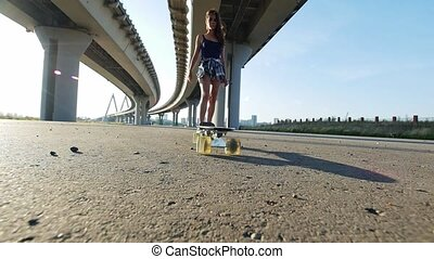 Young girl in short shorts drove a skate leg towards the...