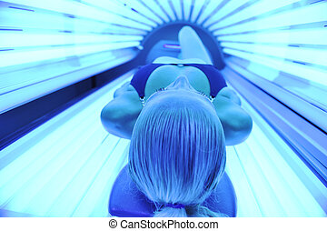 young girl in solarium treatment - young woman at laying on ...
