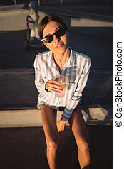 Young girl in sunglasses with a glass of lemonade.