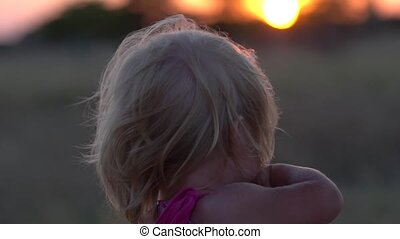 Young girl in the field during sunset. Little girl at sunset close-up.