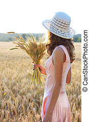 Young girl in the hat and pink dress holding wheat ears in...