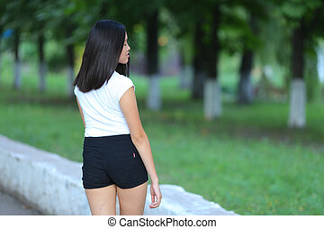 Young girl in the park are walking gait