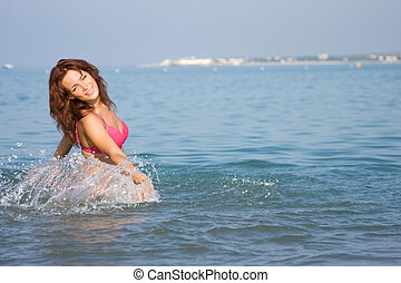 Young girl in the sea, in a spray