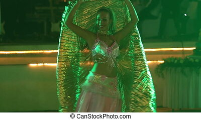 young girl in theatrical costume dances at wedding party