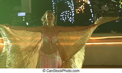 young girl in theatrical costume waves with wings