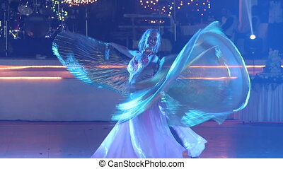young girl in theatrical costume with wings dancing