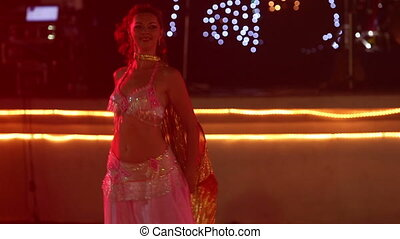 young girl in theatrical costume with wings dances belly dance