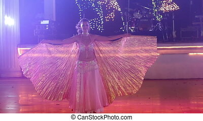 young girl in theatrical wave with wings dancing at wedding party
