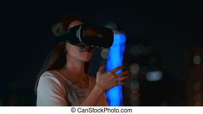 Young girl in virtual reality glasses in a big metropolis -...