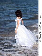 young girl in white dress on the seashore