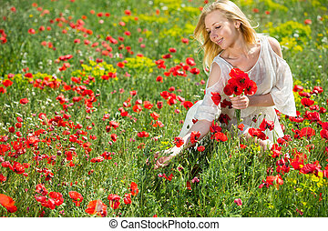 Young girl in white dress picking poppies plants outdoor in fields