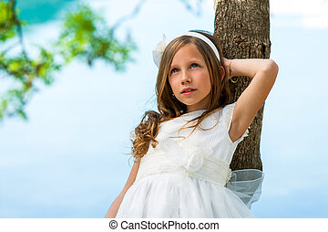 Young girl in white dress resting against tree.