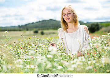 Young girl in white dress sitting in field of wild chamomile flowers
