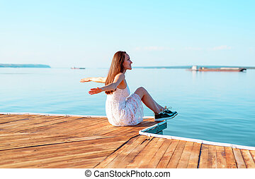 Young girl in white dress sitting on a wooden pier with open hands looking into the distance of the sea, freedom, clean air, dreams