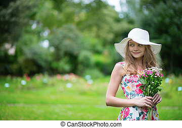 Young girl in white hat holding flowers