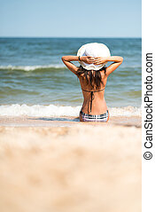 young girl in white hat sitting on the beach