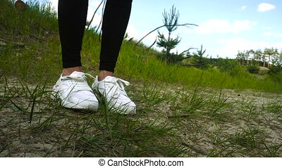 young girl in white sneakers practicing footwork outdoors