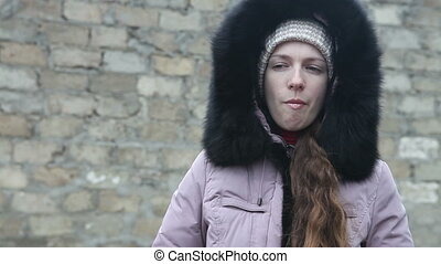 young girl in winter clothes chews the cud