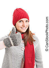 Young girl in winter clothes holding thumbs up