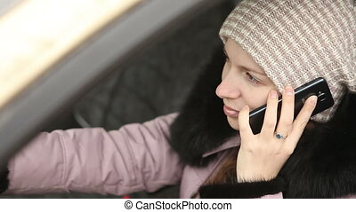 young girl in winter clothes talking on the phone