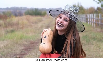 Young girl in witch hat holding pumpkin frightening at camera sitting on autumn nature