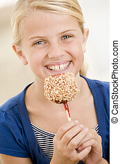 Young girl indoors eating candy apple smiling