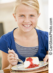 Young girl indoors eating cheesecake smiling