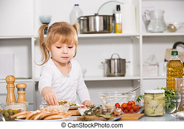 Young girl is cooking vegetables dish alone in the kitchen