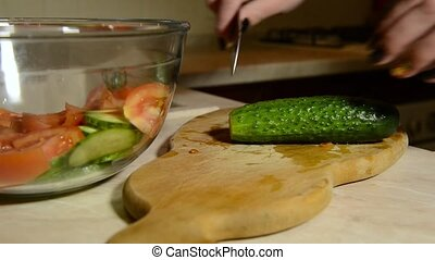 young girl is cutting a cucumber with a knife
