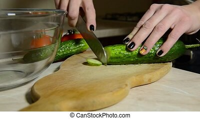 young girl is cutting a cucumber with a knife - young girl...