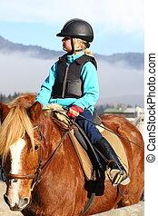 going on horseback - young girl is going on horseback in...