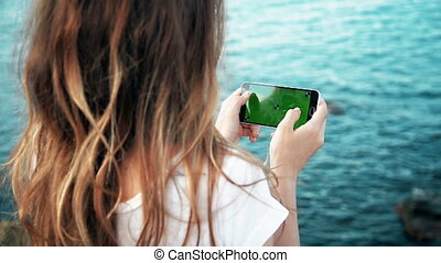 Young Girl is Holding Smartphone with Green Screen at Evening Time Sea