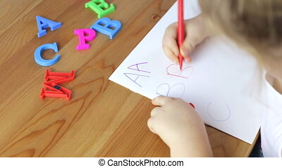 Young girl is learning the alphabet. Writing letters concept
