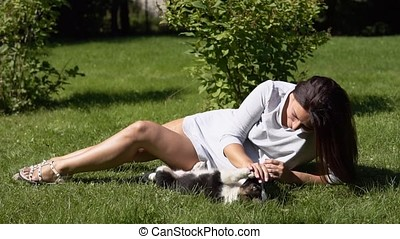 Young girl is playing with a dog in the park on the grass.slow motion.