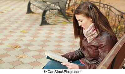 Young Girl Is Reading Book On a Bench In Park