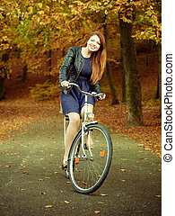 Young girl is riding bike in the park.