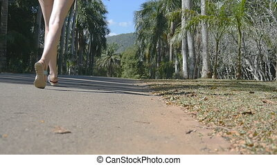 Young girl is running at the park. Woman exercising outdoors, close up. Slow motion