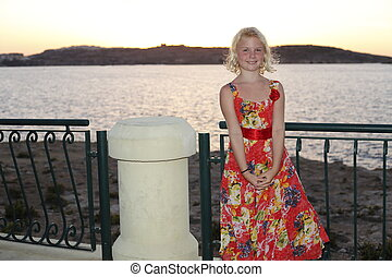 young girl is smiling in front of the sea