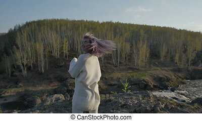 young girl is spinning on a rock in a forest. slow motion
